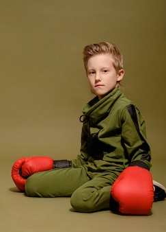 Serious boy on green in red boxing gloves, tired boy