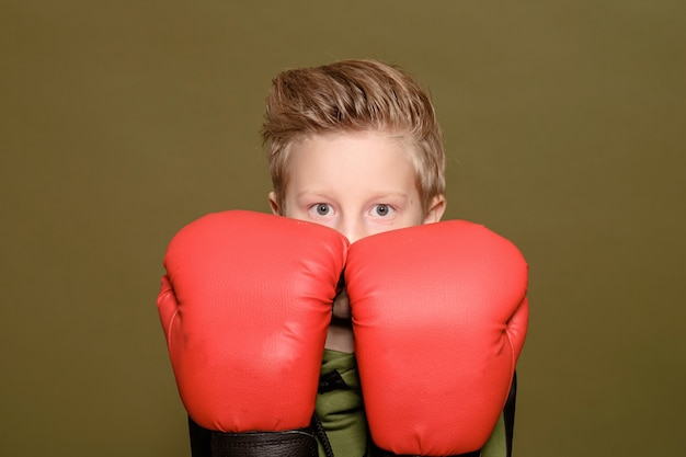 Serious boy on green in red boxing gloves
