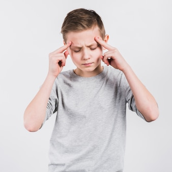Serious boy having headache standing against white background