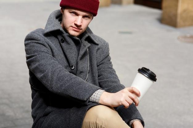 Серьезный мальчик в красной шляпе сидит с чашкой кофе на улице