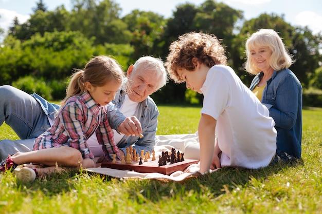 Серьезный мальчик, опираясь на левую руку, сидя рядом со своей бабушкой и глядя вниз на игровую доску