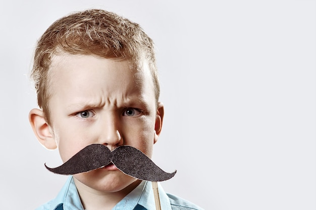 Serious boy with a large moustache frowned against the gray