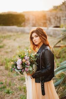 パステルカラーのドレスと花束と黒の革のジャケットの真面目な花嫁