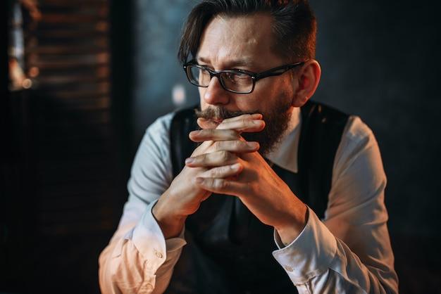 Серьезный задумчивый бородатый мужчина в очках