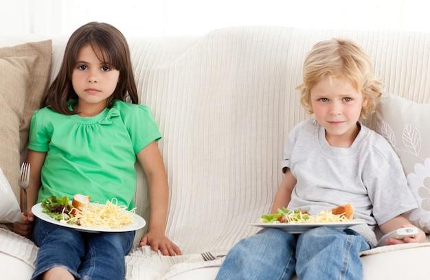 심각한 형제와 자매는 소파에서 저녁을 먹고