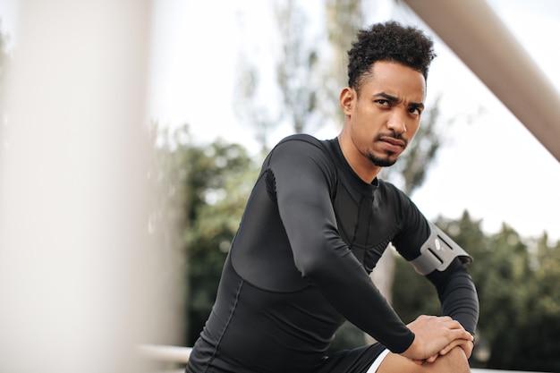黒の長袖tシャツを着た真面目な黒髪の浅黒い肌の男が目をそらし、外の公園で運動するように伸びる