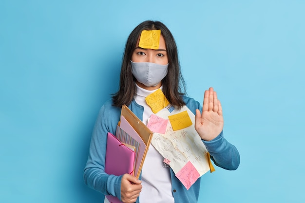 Serious brunette asian woman office worker keeps palm towards in stop gesture, wears disposable mask