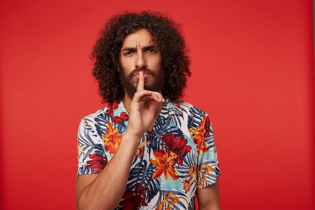 Serious brunette curly bearded guy in multi-colored flowered shirt keeping forefinger on his lips and frowing eyebrows, asking to keep silence, standing against red background