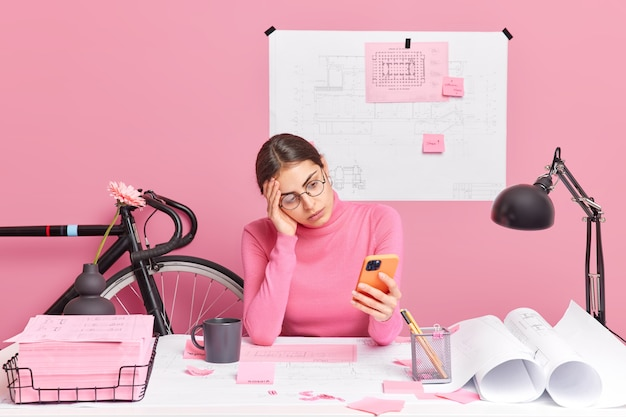 Serious brunette european woman concentrated into smartphone works on new architectural project prepares residence complex