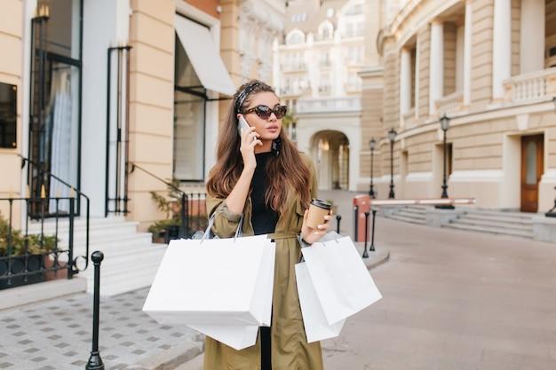 Signora bruna seria fashionista parlando al telefono durante lo shopping nel fine settimana autunnale