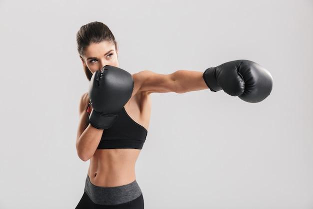 Серьезная брюнетка фитнес женщина тренировки в боксерских перчатках, глядя в сторону, на белую стену