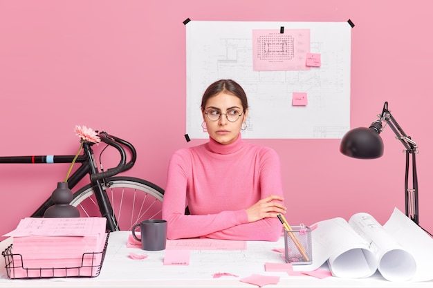 Serious brunette woman architect checks details of blueprint thinks about details of new project sits at desktop drinks coffee wears round spectacles and turtleneck makes model house in office