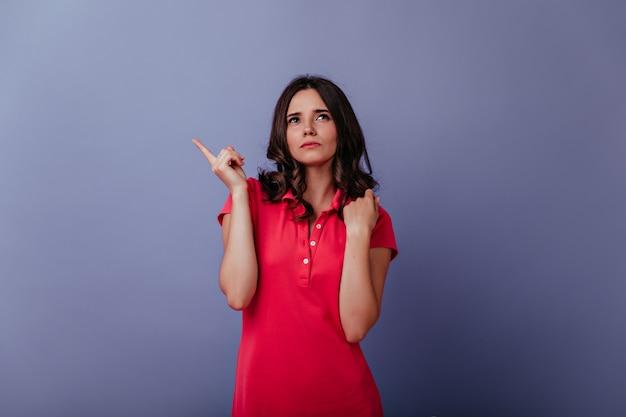 Donna seria del brunette in vestito rosso casuale che osserva in su. ritratto di ragazza glamour pensieroso isolato sulla parete viola.