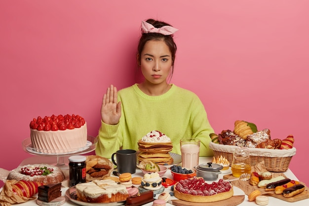 Серьезная брюнетка делает жест отказа, позирует возле кухонного стола с десертами, придерживается диеты, отказывается от калорийной пищи. модные сладкие кондитерские изделия