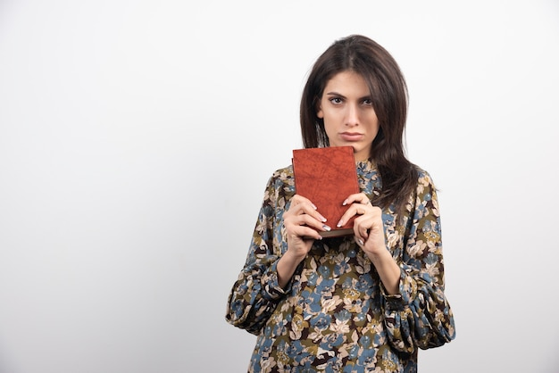 本を見せている深刻なブルネットの女性。