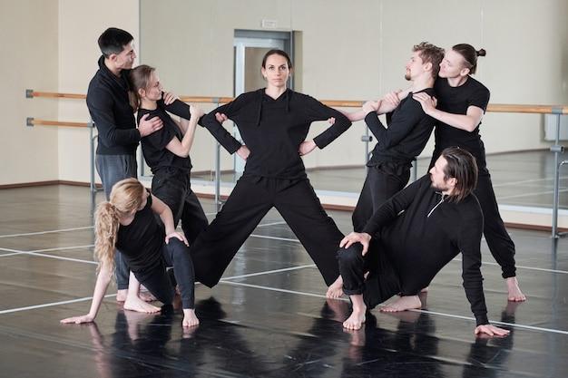 Серьезная брюнетка женщина, стоящая на полу с вытянутыми ногами, пока группа молодых людей тренируется с ней