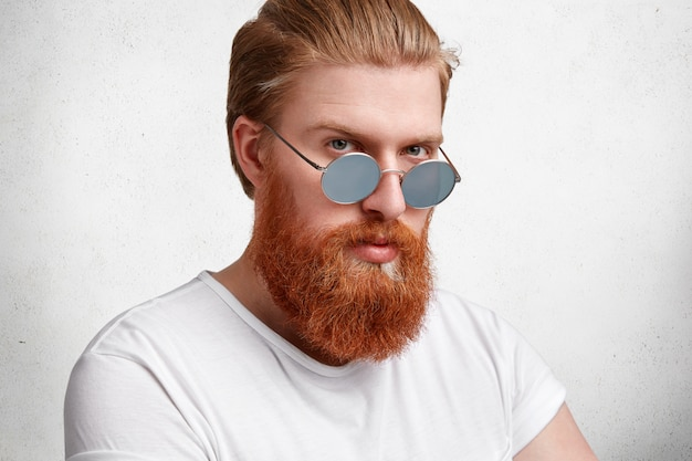 Серьезный брутальный стильный хипстер с модной прической, густой длинной рыжей бородой и усами, уверенно смотрится через солнцезащитные очки.