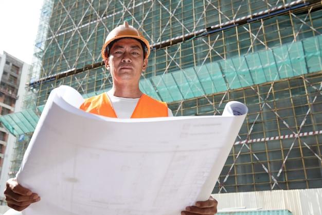 建設現場で働く真面目なビルダー彼は建物の青写真を展開しています