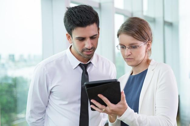 Colleghi di affari seri guardando touchpad