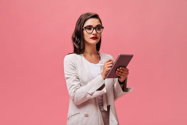 La signora seria di affari con le labbra rosse luminose in occhiali e vestito alla moda beige tiene la compressa su fondo isolato rosa