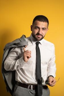 Серьезный деловой человек, одетый в серый люкс, позирует, держа куртку на плече, вешая ее сзади, и солнцезащитные очки в другой руке, глядя вперед с улыбкой, изолированной на желтой стене