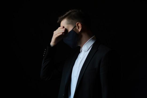 아래를 내려다 보면서 검은 배경에 서있는 검은 양복에 심각한 비즈니스 남자가 고립 된 스트레스를 느낀다.