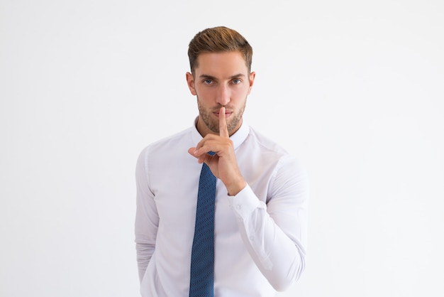 Serious business man making silence gesture