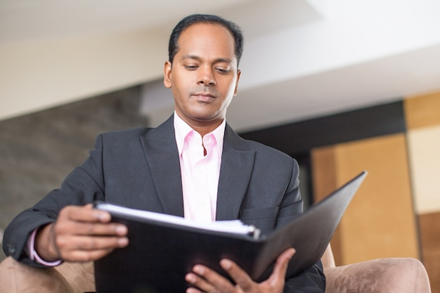 Serious business man reading document in folder