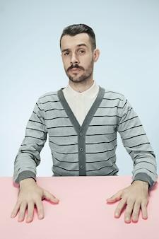 青いスペースのテーブルに座っている真面目なビジネスマン