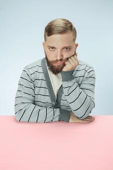 Серьезный деловой человек, сидящий за столом на синем пространстве