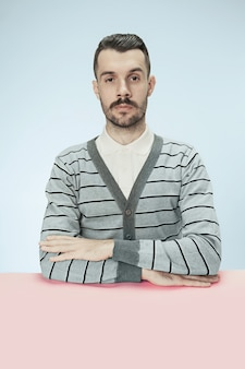 青いスタジオの背景にテーブルに座っている深刻なビジネスマン。ミニマリズムスタイルの肖像画