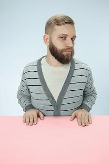 青いスタジオの背景にテーブルに座っている深刻なビジネスマン。
