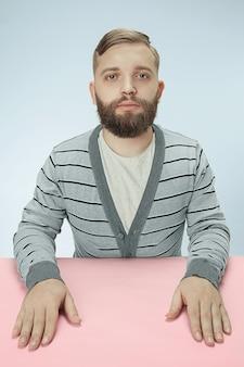 青いスタジオのテーブルに座っている真面目なビジネスマン。