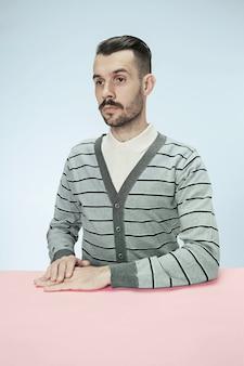 Uomo serio di affari che si siede al tavolo su sfondo blu studio. il ritratto in stile minimalista