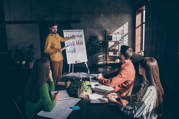 Серьезные деловые люди проходят семинар по современным технологиям предпринимательства с мужчиной, стоящим рядом с диаграммами, показывающими, что их доход увеличился