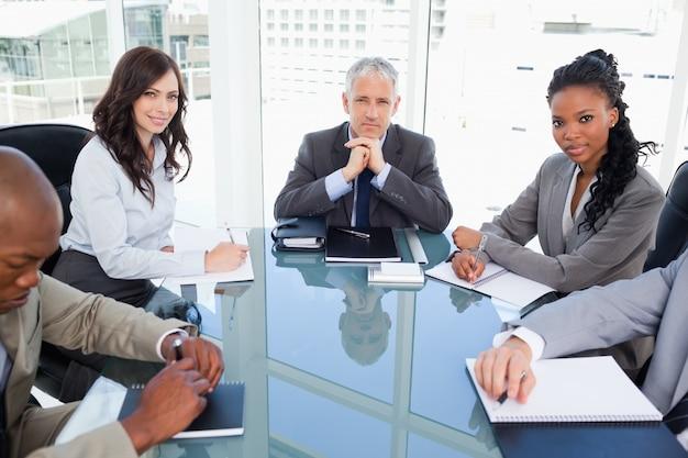 机に座っている間働いている勤勉なビジネスチーム