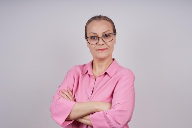ピンクのブラウスを着た、眼鏡をかけた真面目なビジネスウーマン。腕を胸に組んでいる。コピースペースと灰色の背景に孤立した写真。