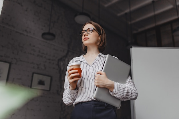 ノートパソコンを保持し、オフィスでコーヒーを飲むスタイリッシュなブラウスと黒のズボンの真面目なビジネス女性。