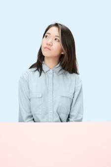 トレンディな青いスタジオの背景に孤立して見上げる、テーブルに座っている深刻なビジネス女性。美しい、若い顔。