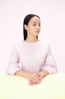 핑크 스튜디오 배경에 테이블에 앉아 심각한 비즈니스 여자. 미니멀리즘 스타일의 초상화