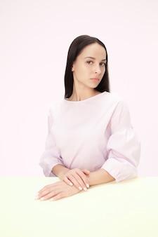ピンクのスタジオの背景にテーブルに座っている深刻なビジネス女性。ミニマリズムスタイルの肖像画