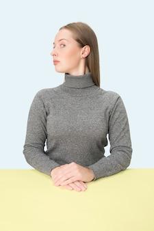 핑크 스튜디오 배경에 테이블에 앉아 심각한 비즈니스 여자.