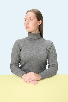 미니멀리즘 스타일의 초상화 테이블에 앉아 심각한 비즈니스 우먼