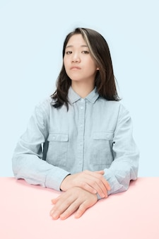 Serious business woman sitting at table, looking at camera isolated on trendy blue studio background. beautiful, young face.