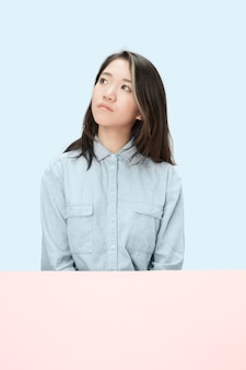 Serious business woman sitting at table, looking up isolated on trendy blue studio background. beautiful, young face.