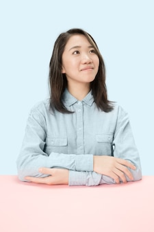 Serious business woman sitting at table, looking up isolated on trendy blue studio background. female half-length portrait.