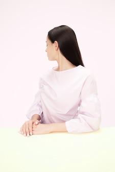 핑크 스튜디오 벽에 테이블에 앉아 심각한 비즈니스 우먼