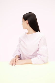 Serious business woman sitting turned away at table on a pink studio wall