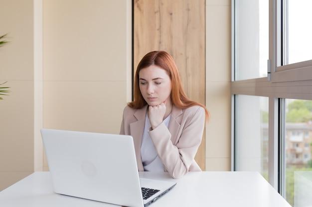 オフィスの机に座ってラップトップに取り組んでいる深刻なビジネス女性