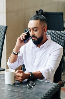 Serious businessman drinking morning coffee and talking on phone with colleague or friend